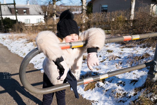 Girl in a furry coat leaning on a metal pedestrian guard rail