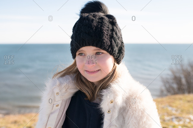 Little girl in a fur coat and toboggan standing on a shore