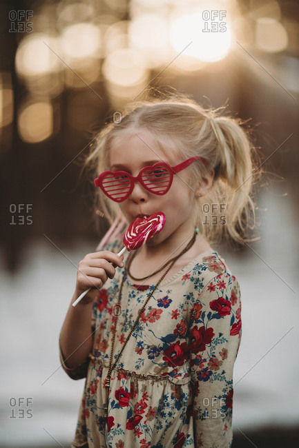 Little girl in heart-shaped sunglasses eating a lollipop