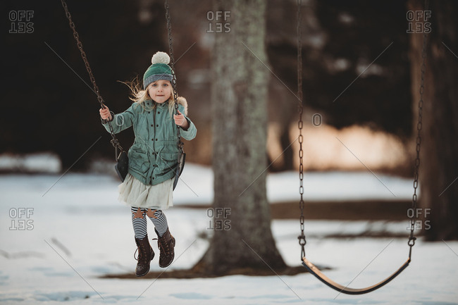 Little girl swinging on a swing in a snow covered park