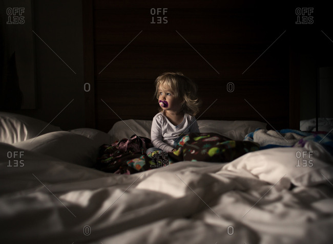 Toddler girl with pacifier sitting on bed in low light