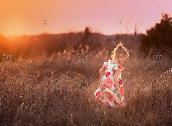 Young girl walking in grassy field at dusk