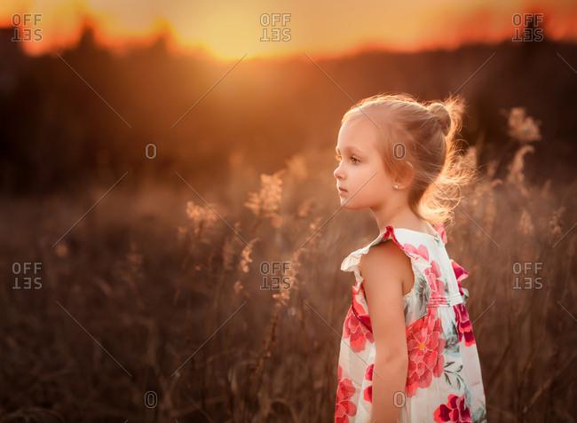 Girl in flowered dress walking in field at dusk