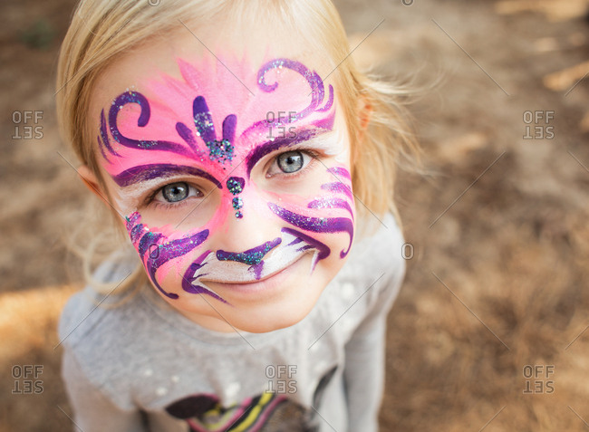 Happy young girl with face painted as purple cat