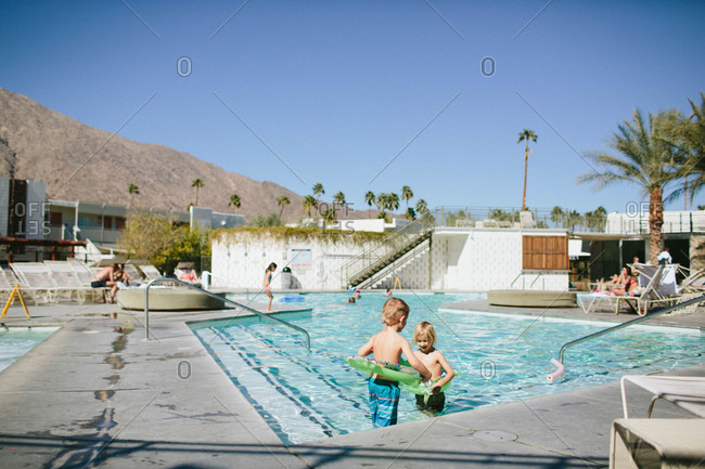 Two boys wearing frog floatation rings swimming in a pool