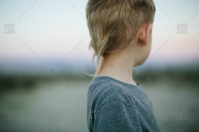 Young boy with blonde hair looking away