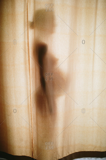 Silhouette of pregnant woman standing behind curtains