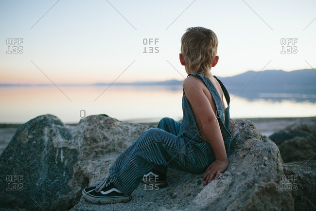 Young boy sitting on rocks by a lake