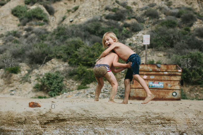 Two boys wrestling on a beach