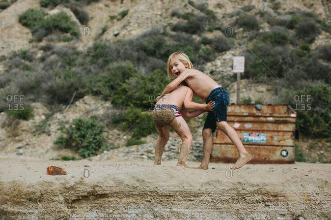 Two boys wrestling on a beach