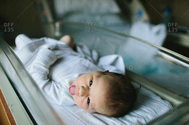 Close up of newborn baby lying in a hospital bassinet