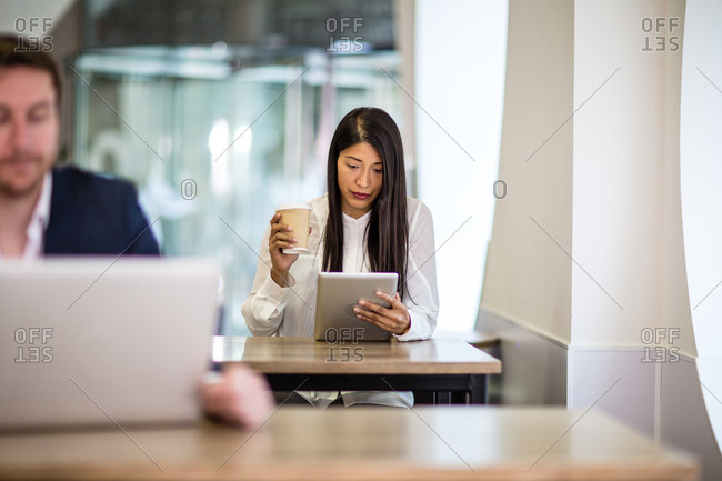 Businesswoman in a cafe reading a digital tablet