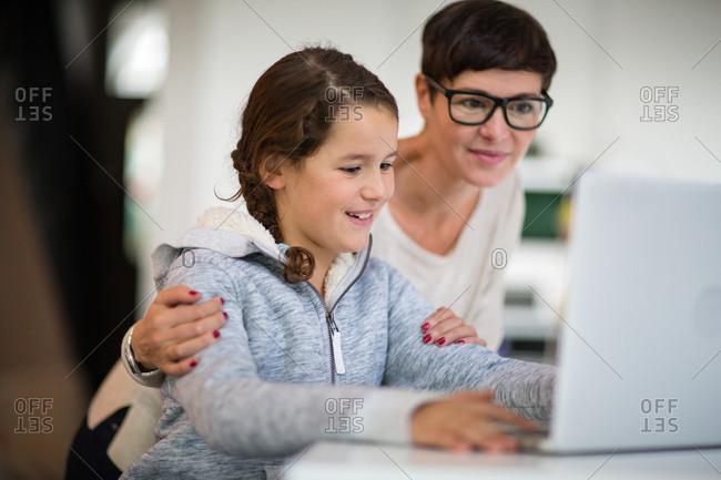 Daughter showing Mom her homework on laptop