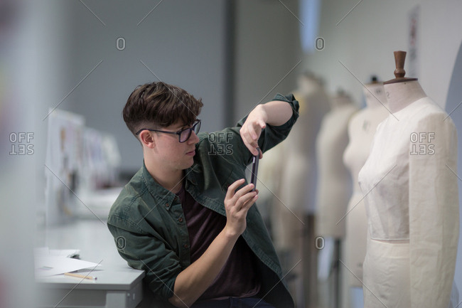 Fashion student taking a photo of a design