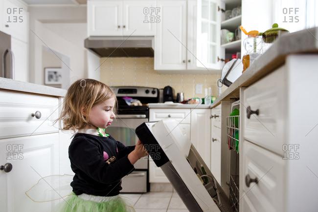 Toddler girl opens dishwasher