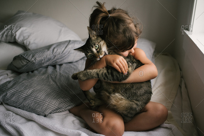 Little girl hugging her cat in bed