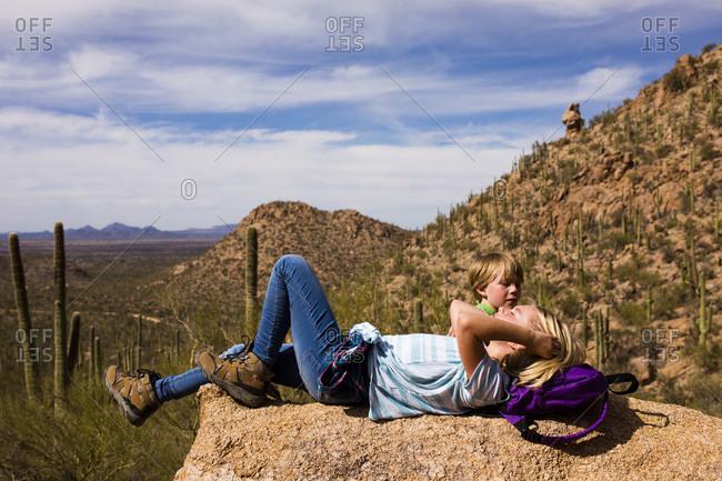 Children relaxing on rock in desert