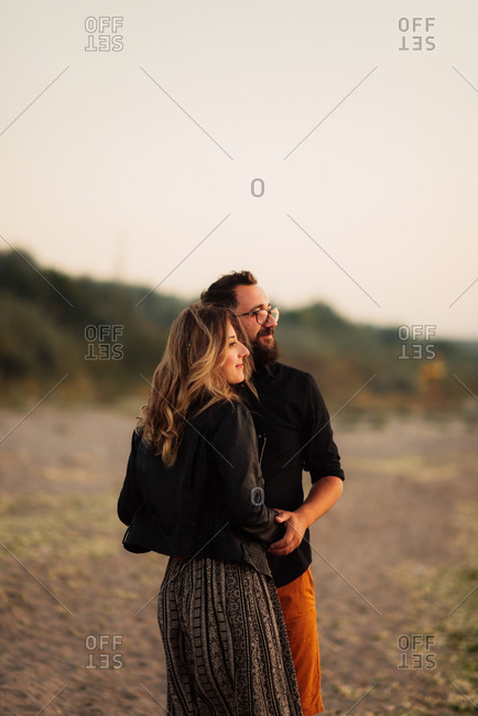 Couple embracing gazing out to sea