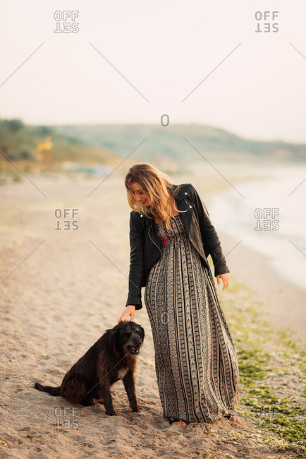 Woman petting a dog on the beach