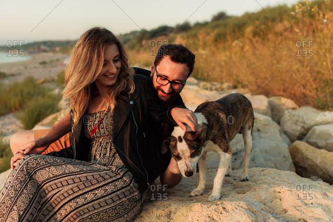 Couple petting dog on coast rocks