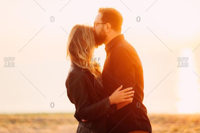 Couple kissing in glowing coastal sunlight