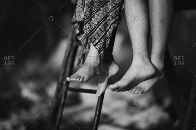 Dangling bare feet of man and woman