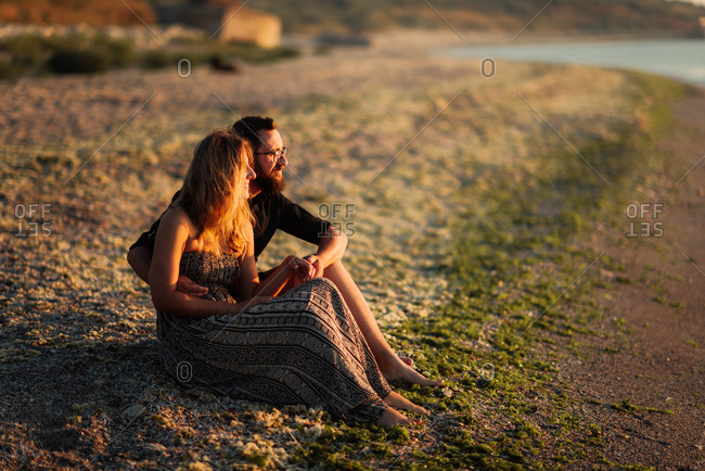 Couple sitting on beach staring out