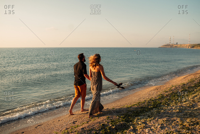 Couple in barefoot stroll on a beach