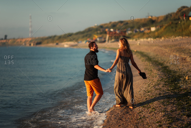 Couple in a barefoot stroll on beach