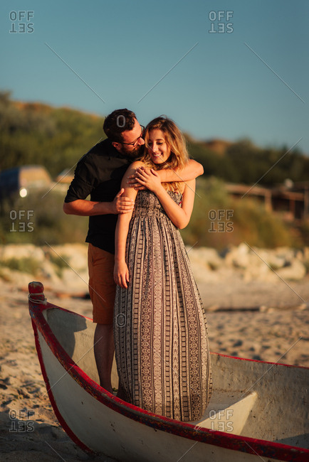 Couple embracing in boat on beach