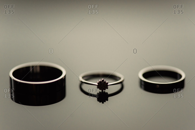 Three wedding bands on mirrored surface