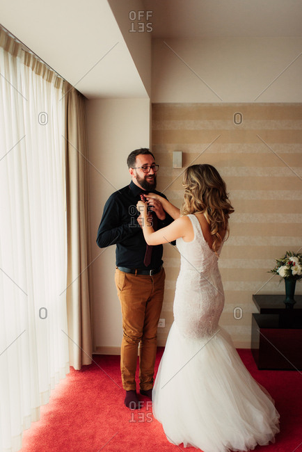 Bride helping groom with tie
