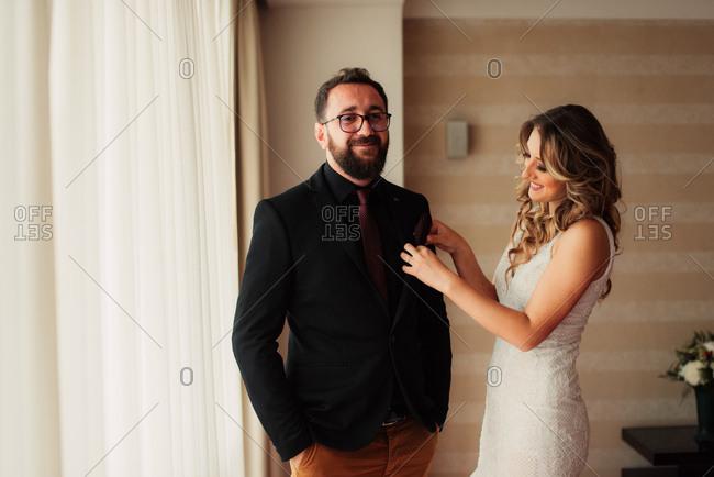 Bride helping groom get dressed