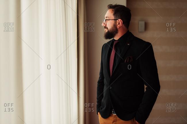 Groom in black blazer looking out window