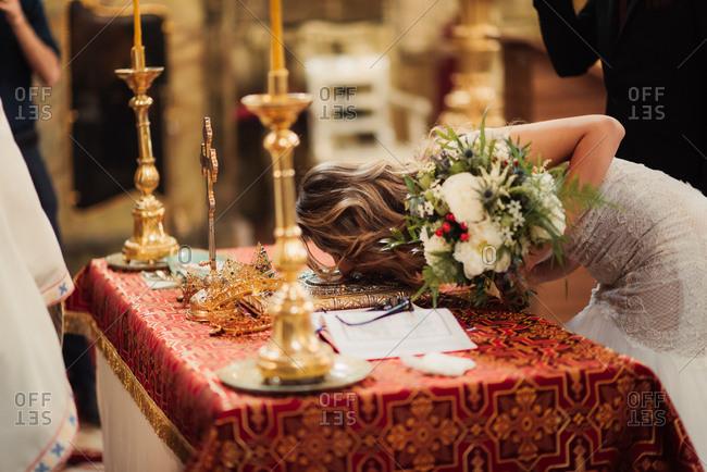 Bride kissing bible during wedding
