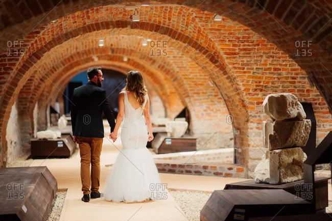 Bride and groom walking in old cellar