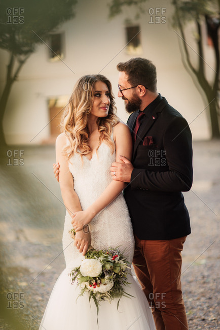Loving bridal couple standing outside