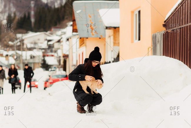 Woman petting cat in snowy town
