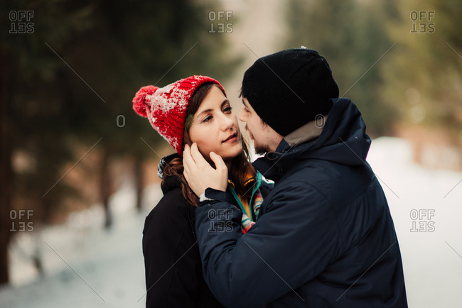 Man touching woman's face in woods