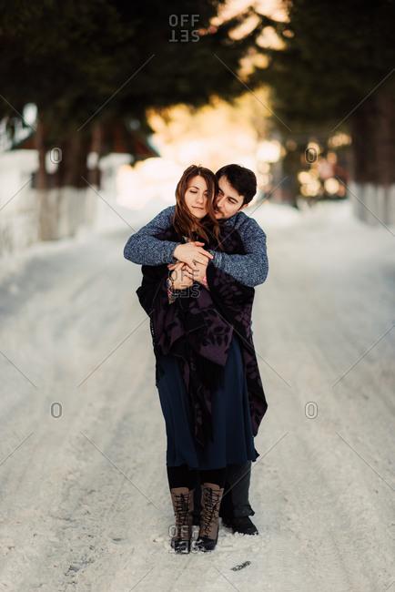 Couple embrace in snowy lane