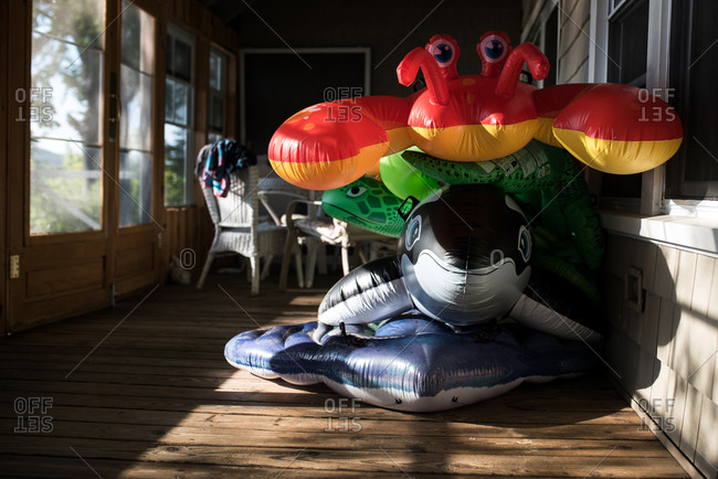 Four pool floats stacked on top of each other on a porch