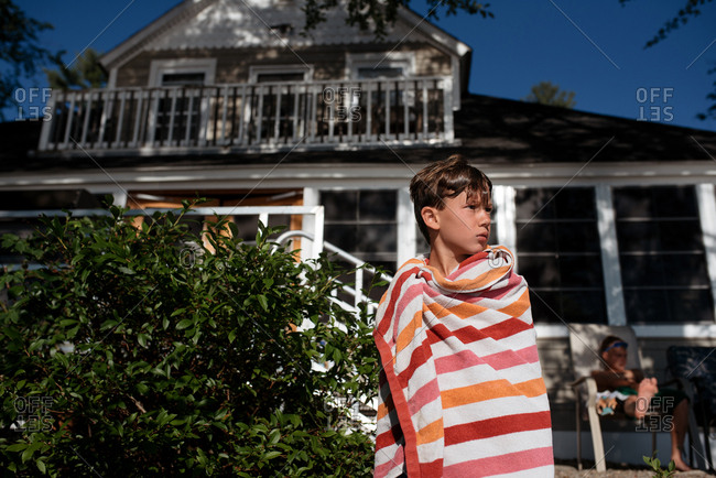 Boy standing in front of house while wrapped in a beach towel