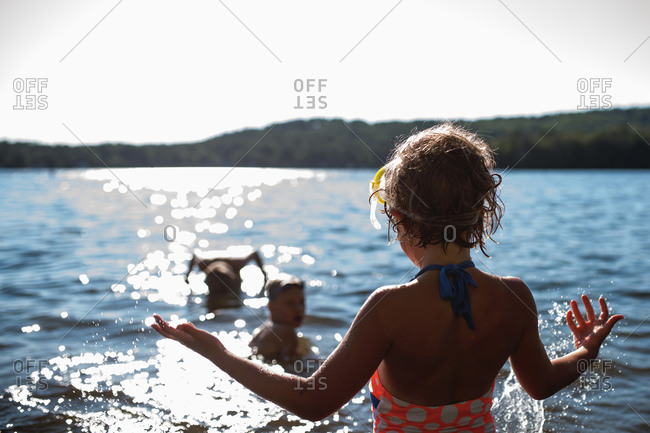 Children swimming in a lake with their dad