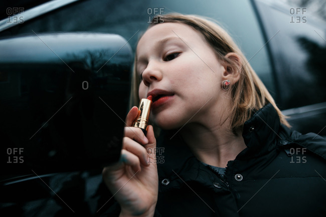 Young girl applying lipstick in car's side view mirror