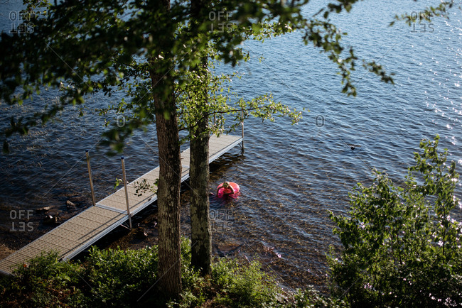 Girl floating alone near a dock on a lake