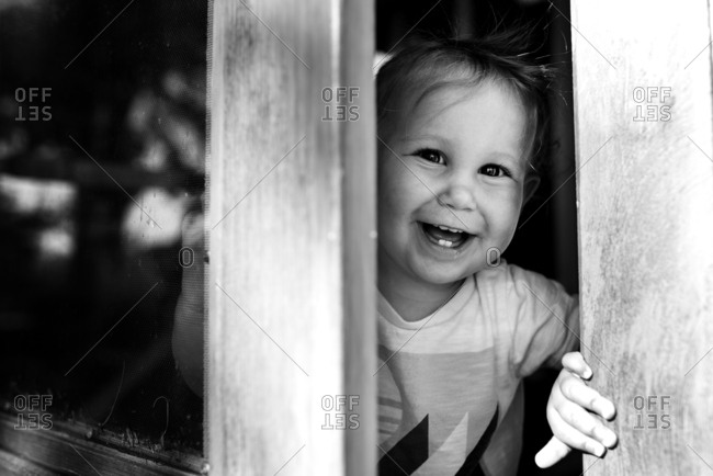 Toddler looking through an open screen door