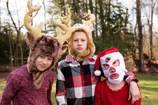 Siblings posing together in silly holiday masks