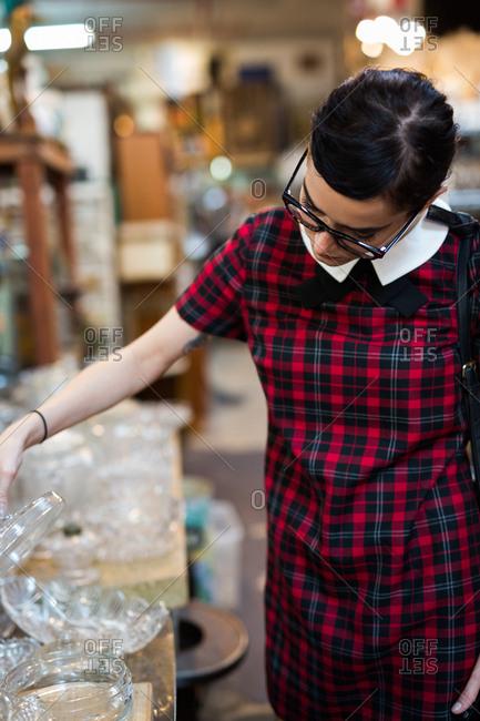Young woman examining glassware