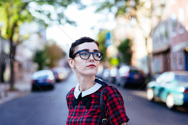 Young woman in glasses lost in her thoughts