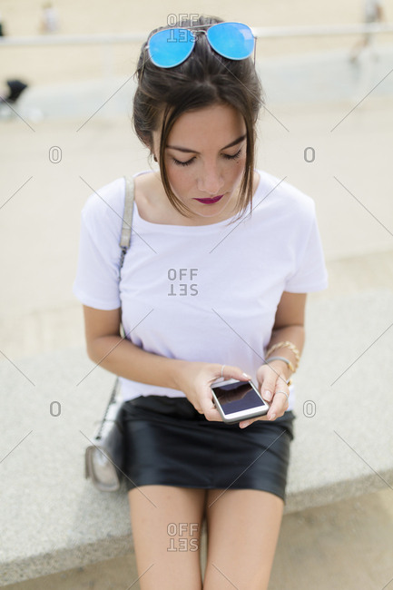 Cool millennial texting at the beach